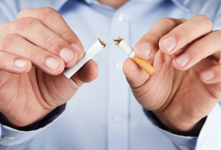 Human hands breaking up cigarette to quit smoking